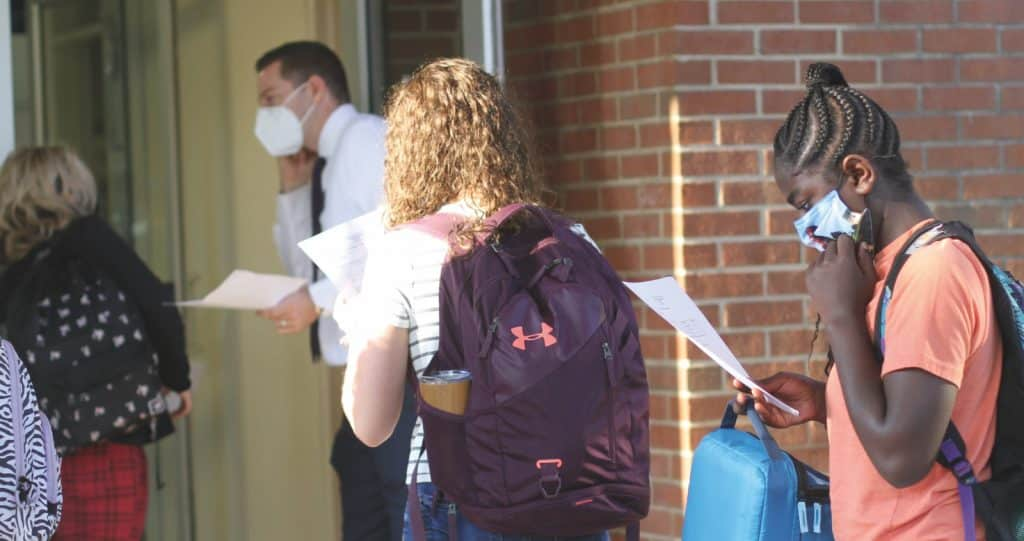Students review their schedules while they await a health screen check in with Justin King, high school principal, on the first day of school.