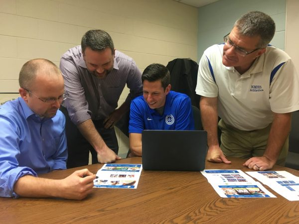 Clay Showalter, Mike Stoltzfus, Andrew Gascho and Dave Bechler review plans for the athletics section of the website, one of the most visited parts of the school's site.