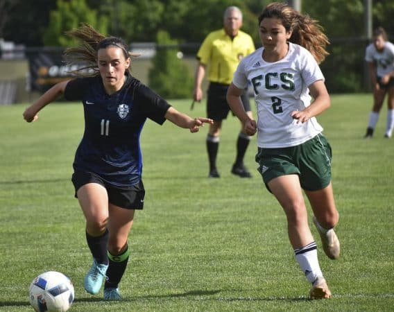 Eastern Mennonite's Ava Galgano (11) gets ahead of Fredericksburg Christian's Catie Jones on Wednesday during the Flames' 2-0 loss in the VISAA Division II girls soccer quarterfinals at EMHS.  Jim Sacco / DN-R