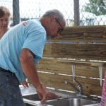 Volunteer Fred Miller builds an outdoor playground learning sink