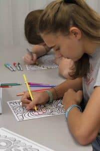 Students quietly color and listen to music during Spiritual Renewal Week Sabbath practices
