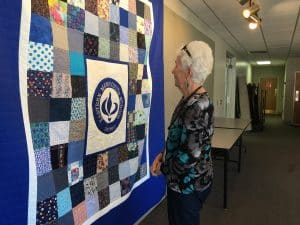 Dorothy Logan looks at the Centennial Quilt that she helped design and stitch