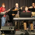 Wes Shuttleworth (seated, at keyboard), music director at UMEI Christian High School, led praise and worship at the Mennonite Educators Conference with fellow music teachers (from left to right) Aaron Johnson, Bethany Christian Schools; Mike Wagner, Hillcrest Academy; Tim Shue, Central Christian School, and Jared Stutzman, Eastern Mennonite School.