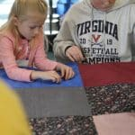 Kindergarten students and eighth graders worked in pairs to knot comforters.