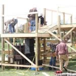 """Fleet of helpers"" constructing multi-level, multi-tier stage to accommodate the required 10-foot distancing."