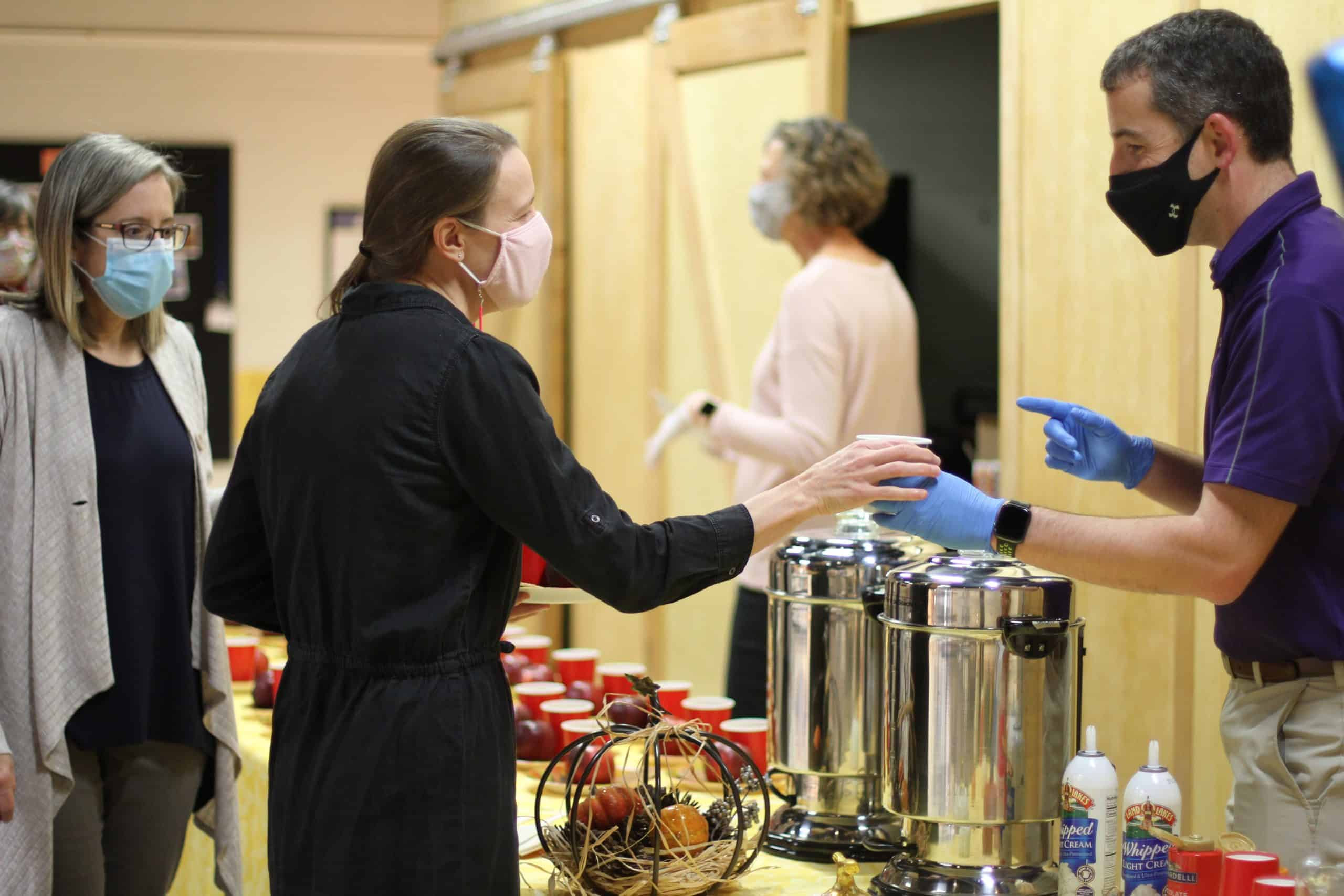 Sarah Mitch, science teacher, receives a beverage from Scott Rogers, board of directors, during a board appreciation event