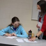 Trisha Blosser, development officer, with a student during Christmas Fund Drive letter writing