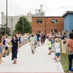 Grades K-4 line the sidewalk to cheer on 5th grade student graduates. Photo courtesy of Christy McKee
